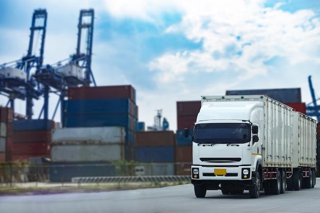 Lading witte containervrachtwagen in scheepshaven logistiek. transportindustrie in havenbedrijf.