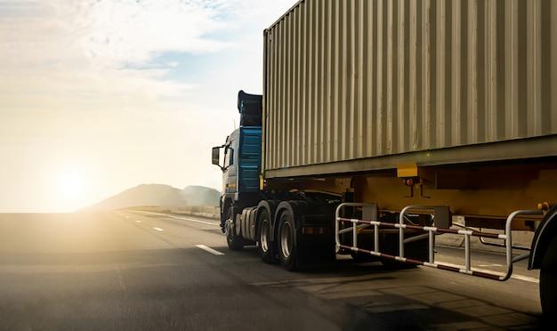 Ladingsvrachtwagen op wegweg met container, vervoer op de snelweg. vrachtwagenonduidelijk beeld aan zachte nadruk