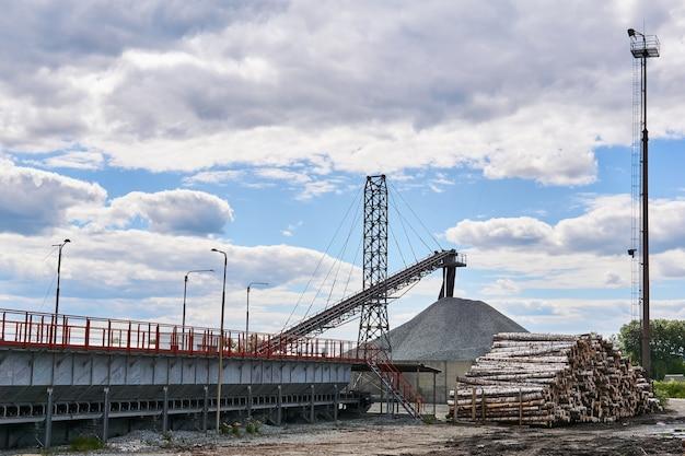 Ladingwerf van de houtverwerkende industrie met stammen en laadbanden