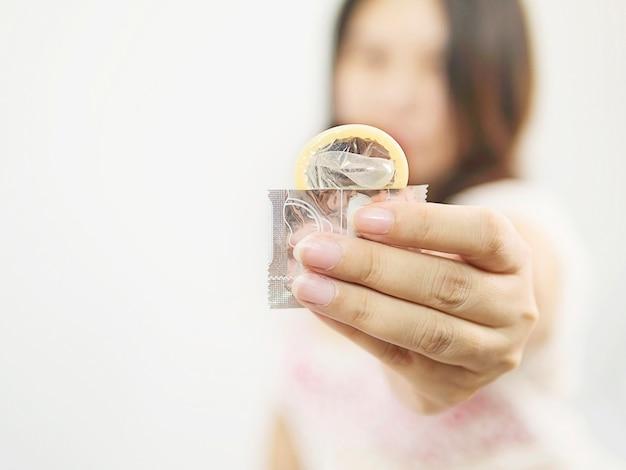 Lady geeft condoom, veilige seks en anticonceptie-concept.