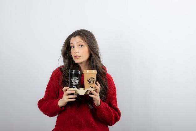 Lady houdt koffiekopjes op kartonnen houder.