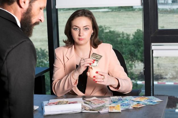 Lady insuit met bruin haar zet 1 amerikaanse dollar biljet in spaarvarken. bebaarde charmante joodse man