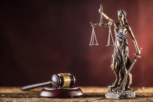 Lady justicia met zwaard en schaal bronzen beeldje met rechterhamer op houten tafel.