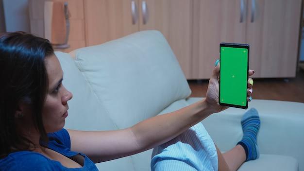 Lady lezen op smartphone monitor met groen scherm liggend op de bank in de woonkamer. vrouw met een mobiele telefoon met mockup-sjabloon chromakey geïsoleerde mobiele telefoonweergave met behulp van techology internet