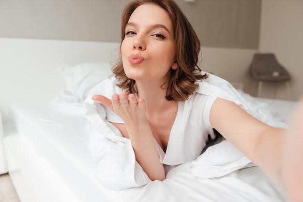 Lady ligt op bed binnenshuis thuis kusjes naar je blazen.