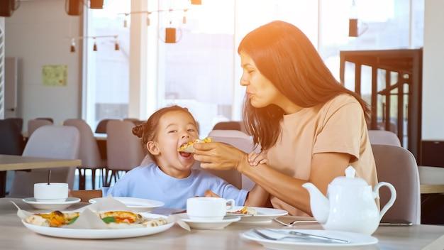 Lady moeder houdt pizzapunt vast en dochter eet in café
