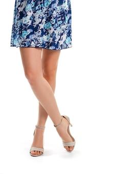 Lady's benen in hakken. beige schoenen en korte jurk. zomers kledingstuk met bloemenpatroon. gemak en comfort.