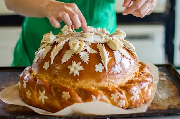 Lady's hand aanraken van versierd gebak. brood op dienblad. mooi bruidsbrood. blijf trouw aan tradities.