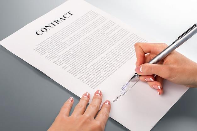 Lady's hand ondertekening promotiecontract. vrouwelijke hand ondertekent promotiecontract. wij zullen je helpen. bedrijven moeten elkaar helpen.