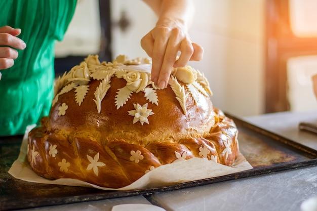 Lady's hand raakt versierd gebak. brood op ovenschaal. professionele bakker maakt bruidsbrood. schotel voor een ceremonie.