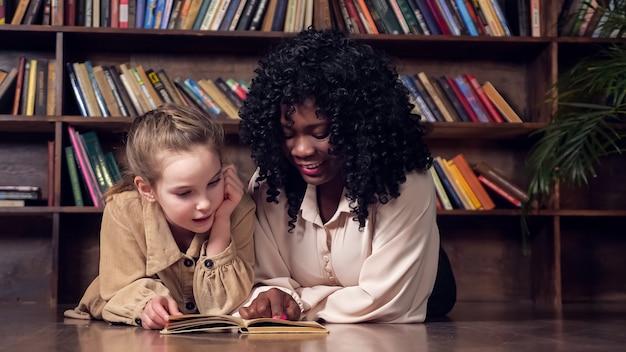 Lady tutor met krullend haar leert schoolmeisje leesboek