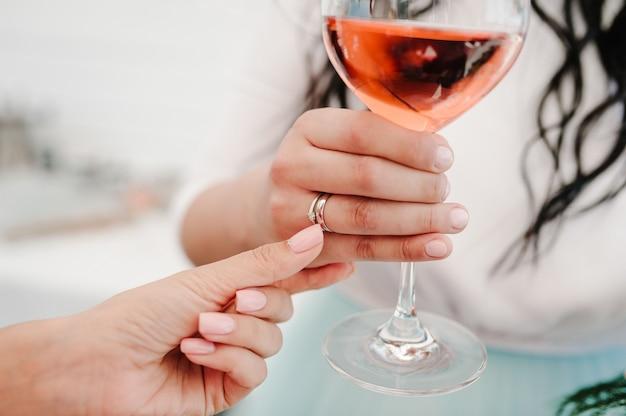 Ladys hand met een glas wijn met een trouwring op vinger op feestje.