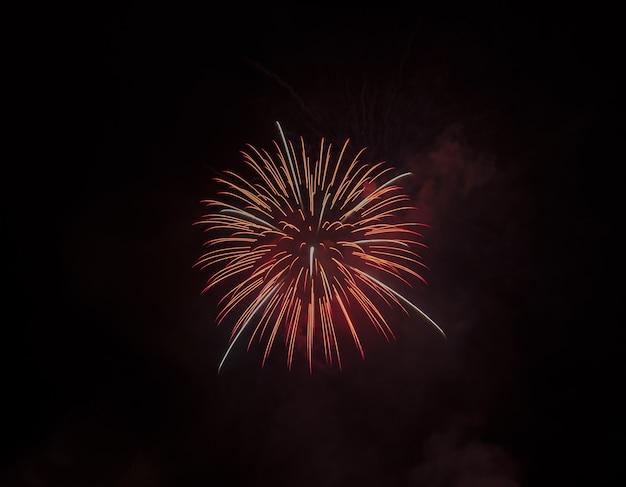 Lage die hoek van een mooi rood vuurwerk is ontsproten dat op zwarte hemel wordt geïsoleerd
