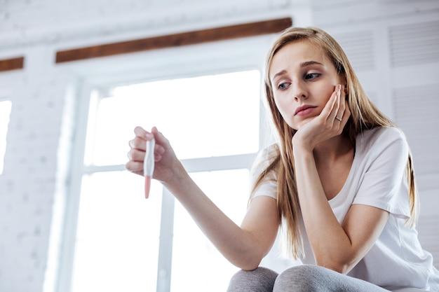 Lage geesten. unsmiling jonge vrouw zitten en houdt haar zwangerschapstest