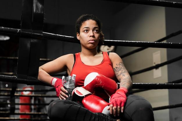 Lage hoek atletische vrouw die een onderbreking van het uitoefenen neemt