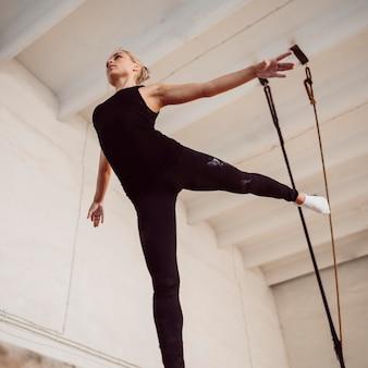 Lage hoek atletische vrouw training op evenwichtsbalk