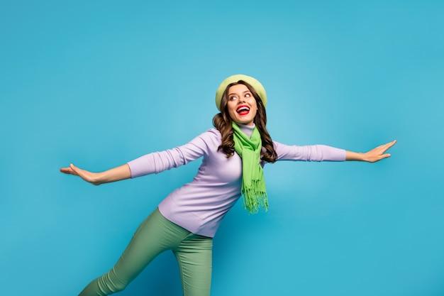 Lage hoek bekijken foto van charmante mooie dame reiziger lopen straat vangen taxi auto opgewonden stemming dragen groene baret hoed paarse trui sjaal broek geïsoleerde blauwe kleur muur