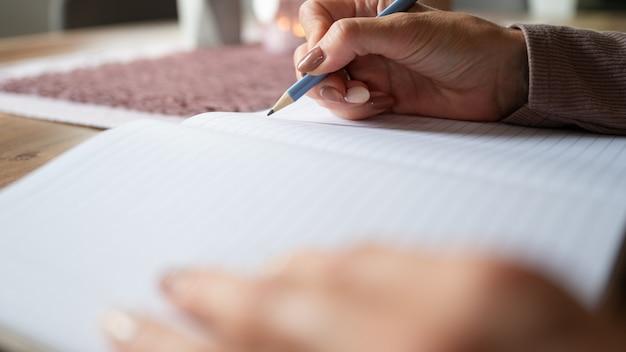 Lage hoek close-up weergave van vrouwelijke handen schrijven in notebook thuis.