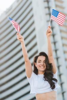 Lage hoek die donkerbruine vrouw glimlacht die twee vlaggen van de vs houdt