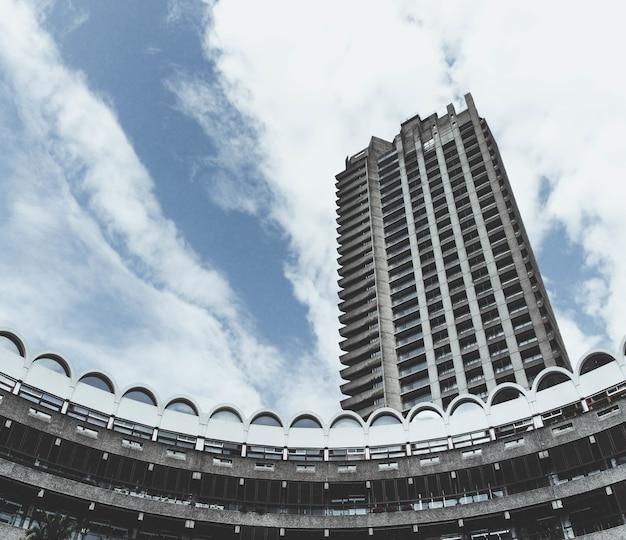 Lage hoek die van barbican centre in londen met een bewolkte blauwe hemel is ontsproten