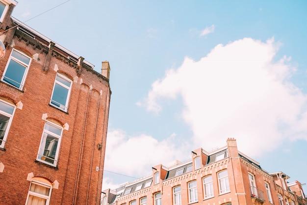 Lage hoek die van bruine concrete gebouwen is ontsproten onder de bewolkte hemel