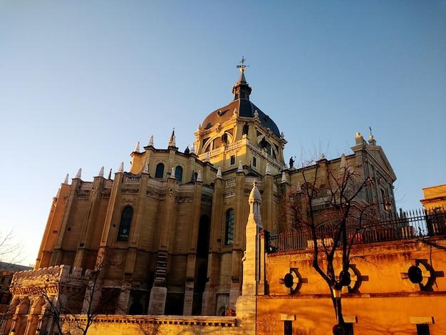 Lage hoek die van de almudena-kathedraal in spanje onder een blauwe hemel is ontsproten