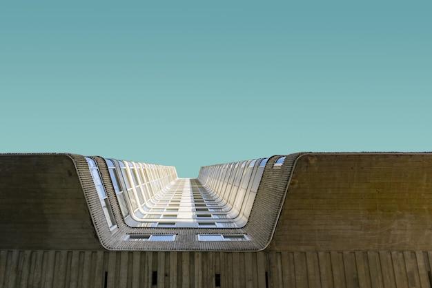 Lage hoek die van de hoge baksteenbouw onder de duidelijke blauwe hemel is ontsproten