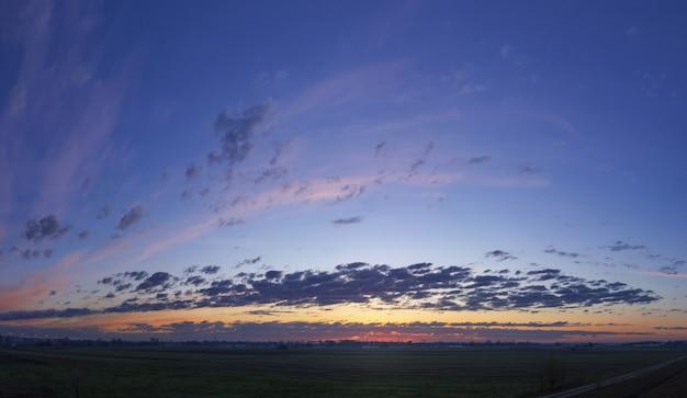 Lage hoek die van de mooie hemel met wolkenvormingen is ontsproten tijdens zonsondergang
