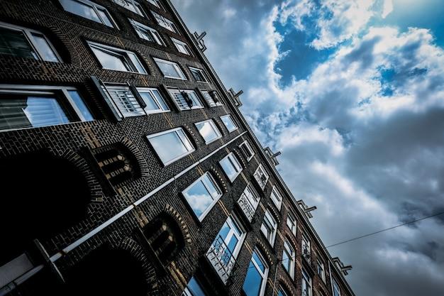 Lage hoek die van een baksteengebouw is ontsproten met vensters en een bewolkte hemel