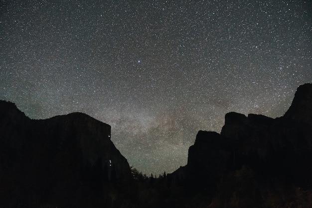 Lage hoek die van een bergachtig landschap onder de magische nachthemel is ontsproten