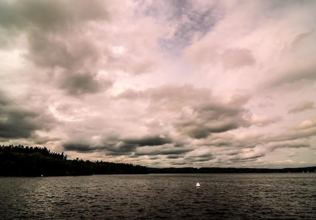 Lage hoek die van een bewolkte hemel in de oceaan is ontsproten