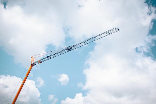 Lage hoek die van een bouwkraan is ontsproten onder een bewolkte hemel