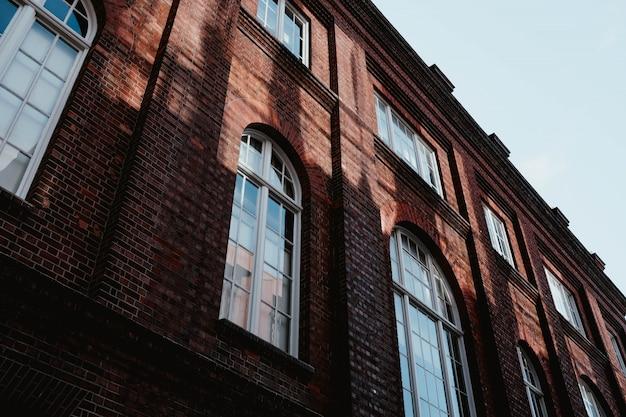 Lage hoek die van een bruin concreet gebouw met boogvensters is ontsproten
