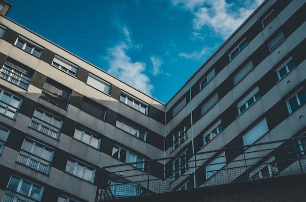 Lage hoek die van een bruin en wit gebouw met vensters onder een blauwe hemel is ontsproten