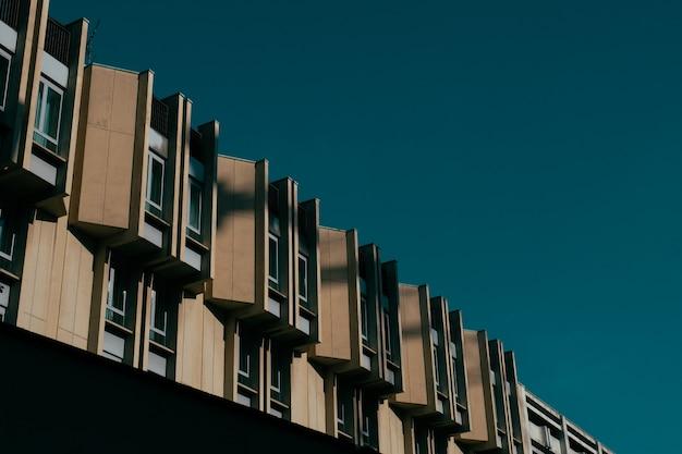 Lage hoek die van een bruin gebouw met vensters en een donkerblauwe hemel is ontsproten