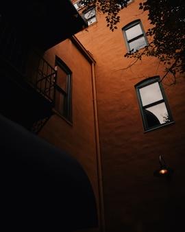 Lage hoek die van een bruin gebouw met verticale vensters is ontsproten
