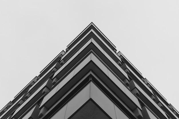 Lage hoek die van een grijs concreet gebouw is ontsproten dat moderne architectuur vertegenwoordigt