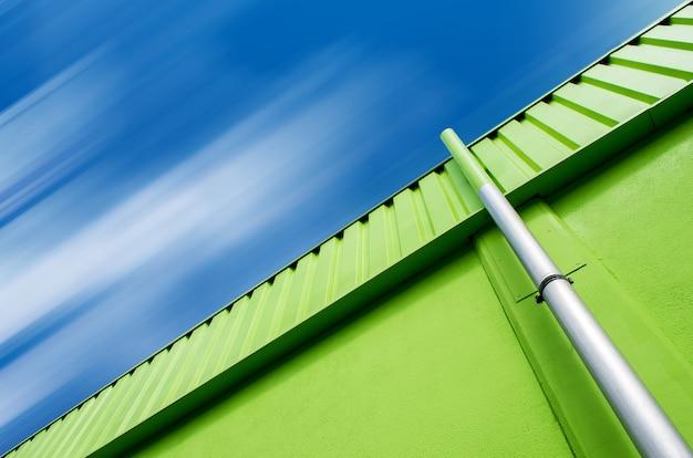 Lage hoek die van een groen gebouw met een grijze pijp onder de bewolkte hemel is ontsproten