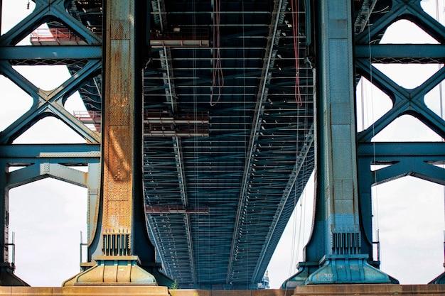 Lage hoek die van een grote blauwe metaalbrug is ontsproten op een zonnige dag