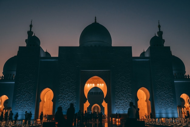 Lage hoek die van een grote moskee in abu dhabi met gloeiende lichten binnen een gebouw is ontsproten