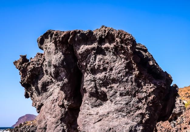 Lage hoek die van een grote rots op een strand met een duidelijke blauwe hemel is ontsproten
