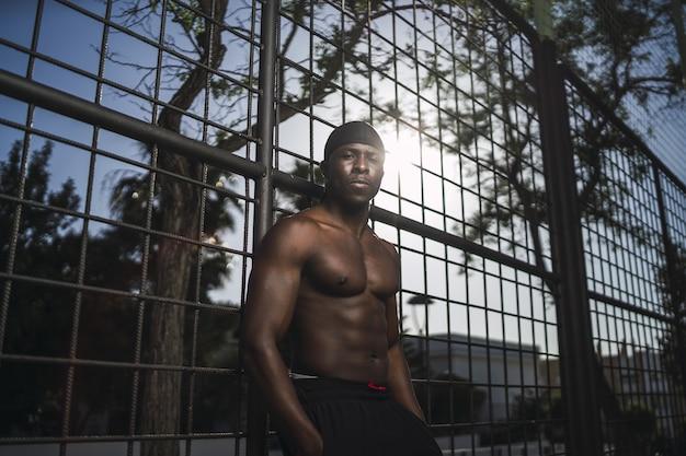 Lage hoek die van een halfnaakte afrikaans-amerikaanse man is ontsproten, leunend op het hek bij het basketbalveld