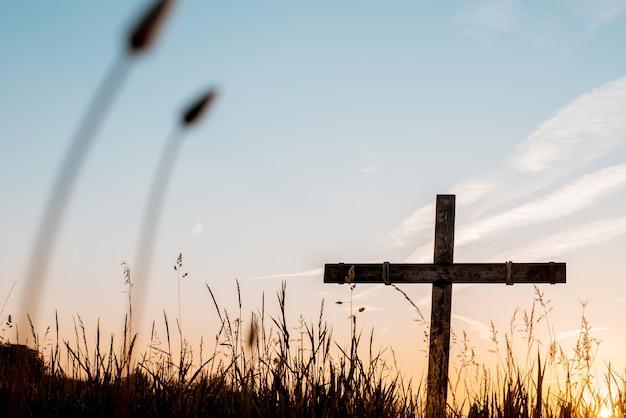 Lage hoek die van een handgemaakt houten kruis in een grasrijk gebied met een mooie hemel is ontsproten