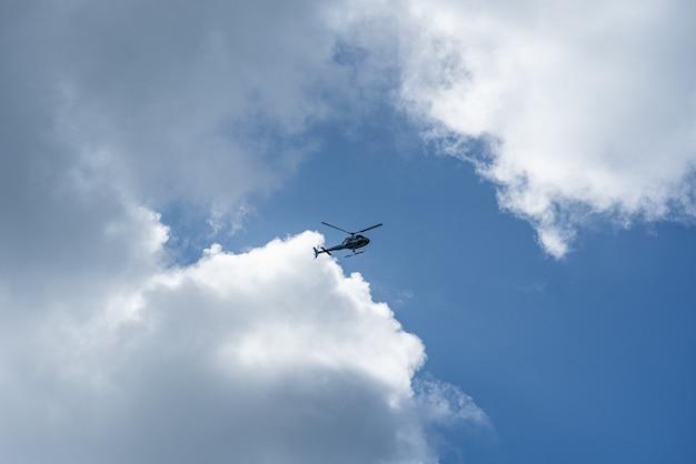 Lage hoek die van een helikopter in de bewolkte hemel is ontsproten