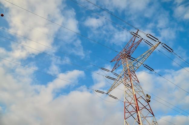 Lage hoek die van een hoge transmissietoren is ontsproten met een bewolkte blauwe hemel in