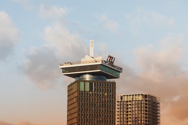 Lage hoek die van een hoog historisch gebouw onder een bewolkte hemel in amsterdam is ontsproten