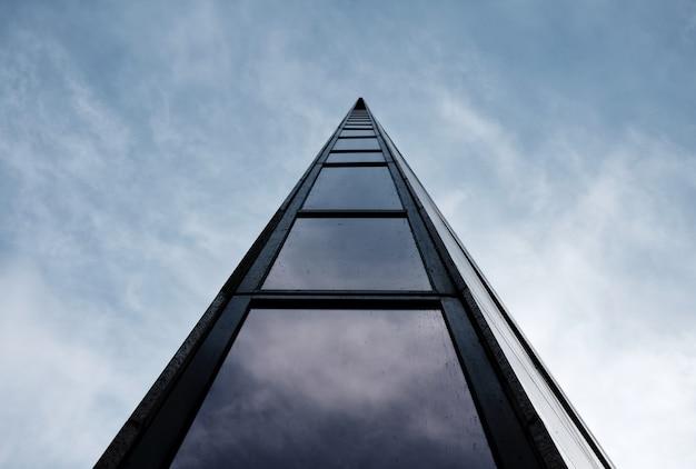 Lage hoek die van een hoog modern architectonisch gebouw is ontsproten met een bewolkte hemel