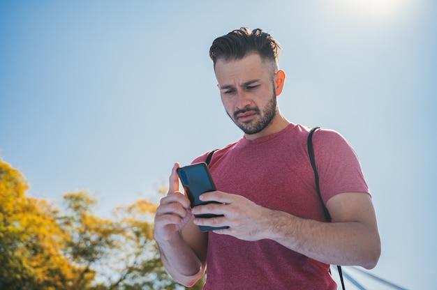 Lage hoek die van een jonge mens is ontsproten die zijn telefoon controleert alvorens te trainen