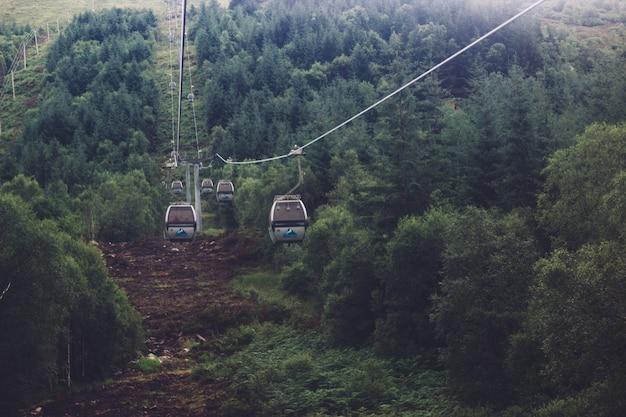Lage hoek die van een kabelbaan in het midden van een groen bergachtig landschap is ontsproten