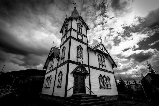 Lage hoek die van een kerk onder een bewolkte hemel in zwart-wit is ontsproten